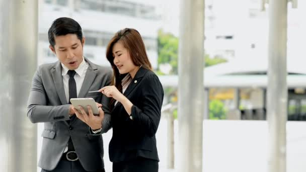Young generation business team concept. Young business intern woman using tablet with her male manager before going to meet client in office for the first time. Taking in business district.