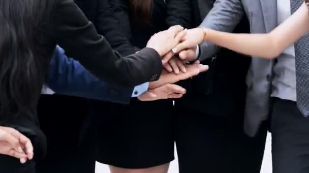 Motivační business týmu stojí v kruhu s rukama dohromady tým mluvit, venku ve městě za jasného slunečného dne, střední záběr Pov.