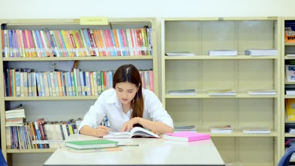 Young student study hard in library. Asian female university student doing study research in library with books on desk and smiling. For back to school education diversity concept.