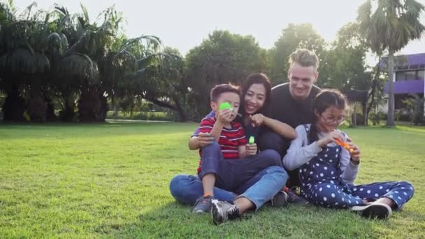 Family blowing bubble in park. Mixed race family with white man, chinese woman and their children. Sitting together on grass in park having fun together.