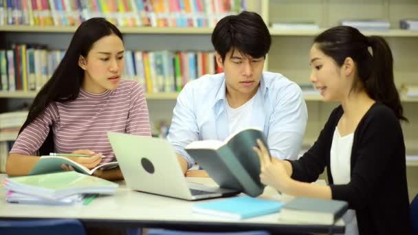 Fiatal diákok tanulmányi kemény könyvtárban. Boldog ázsiai női és férfi egyetemi hallgatók tanulmányi csinál kutatás a könyvtár könyveket a iskolapad, jegyzetfüzet. A vissza az iskolai oktatás sokszínűség koncepció.