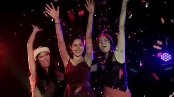 multiethnische Gruppe schöner Frauen, die mit Freunden auf der Tanzfläche eines Nachtclubs mit herabfallendem Konfetti fröhliche Partymusik tanzen. Mittlerer Schuss, Zeitlupe.