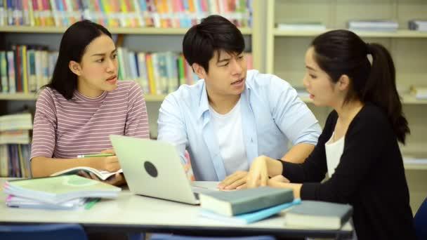 Mladí studenti se pilně studovat v knihovně. Happy asijské ženské a mužské vysokoškolských studentů dělá studie výzkum v knihovně knihy na stole, poznámkového bloku. Pro zpátky do školy rozmanitost koncepce.