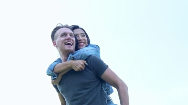 Happy Couple having fun outdoors. Laughing joyful family, white man and chinese woman. Freedom concept. Super slow motion.