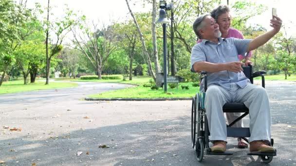 Starší dvojice v parku a na kolečkovém křesle. Čínský starý pár v parku, uklidňující, s úsměvem. Muž na kolečkovém křesle se svojí ženou. Kopírovat místo.
