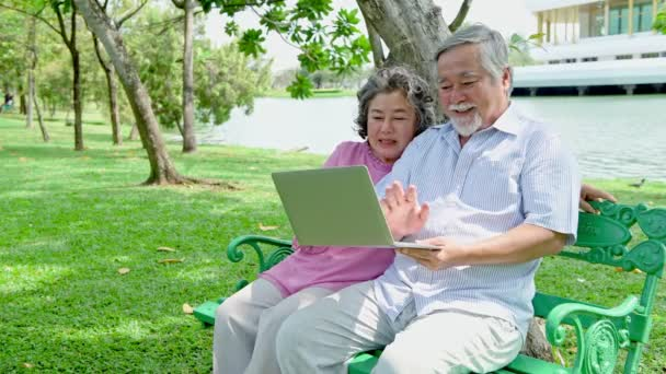 Senior couple in park. Looking at notebook and talking to each other and having fun. Sitting on bench. Chinese old people.