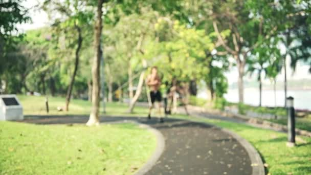 Man running in park. Shirtless very fit white man with six pack abs running in park in afternoon and stop by looking at his fitness smart watch. Modern fitness technology concept.