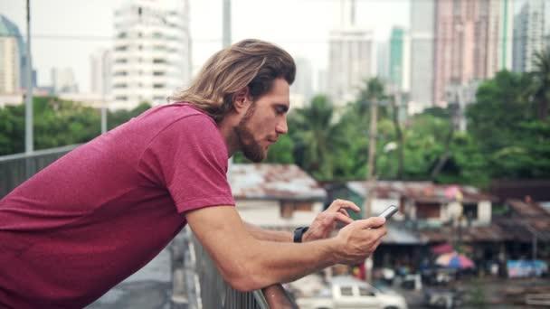 Mladý muž pomocí chytrého telefonu v městské zástavbě. Bílý muž veřejných nadjezdu pomocí chytrého telefonu ke kontrole jeho oznámení. Mobilní technologie koncept.