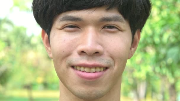 Attractive young man portrait. Chinese man with black hair in his early 20s smiling. Laughing and smile at the camera.
