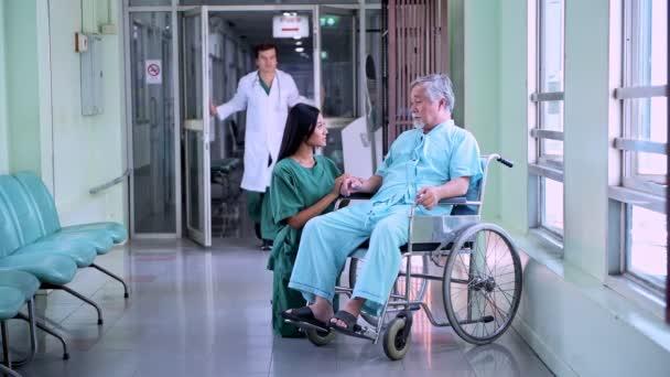 Starší pacient na vozíku s jeho krásná sestra. Krásná Čínská žena uklidňující starý Číňan v invalidním vozíku s lékařem a žena pěší průchod v nemocniční chodbě