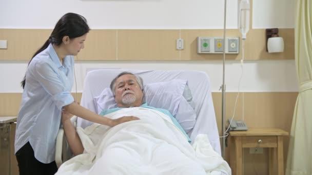 Smutné, starší pacient v posteli s jeho dcerou. Lékař a sestra mu říká špatné zprávy starší muž v šoku se svou dcerou se snaží ho v nemocnici.
