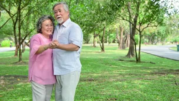 Sladký starší pár tancuje v parku. Starý asijský muž a žena tančí společně v parku a stojí. Koncepce staršího životního stylu.