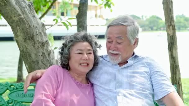 Édes Senior pár pihentető parkban. Régi ázsiai férfi és nő ül padon pihentető és beszélgetett. Senior életmód koncepció.