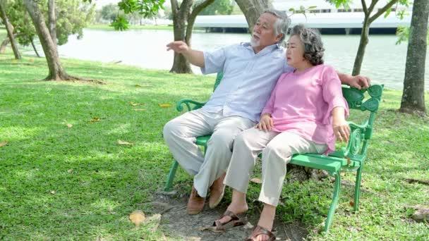 Senior pár parkban. Doing selfie és beszélgetett egymással és a szórakozás. Ül a padon. Kínai öregek.