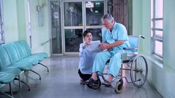 Paziente anziano felice in sedia a rotelle con la sua bella figlia. Bella donna cinese confortante uomo cinese anziano in sedia a rotelle con medico e infermiera a piedi passa in corridoio dellospedale. Dolly shot.