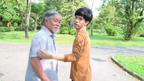 Apa és fia Park portré. Nyugalmazott kínai apa és fia tartja egymást, boldog és mosolygott. Sikeres családi szeretet és kapcsolatkoncepció.