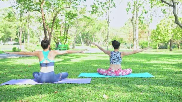 Nő tanít jóga parkban. Jóga és pihenés a közparkban.