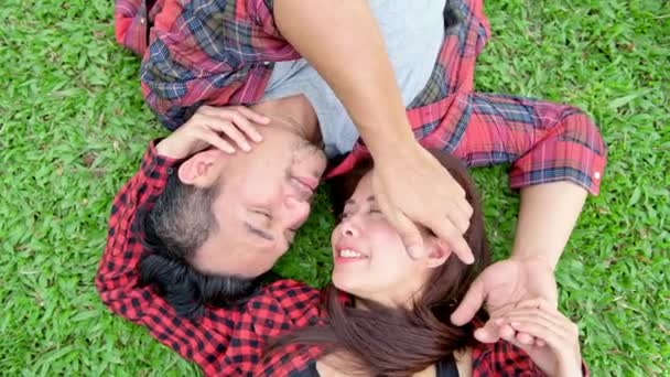 Romantic couple in park. Chinese asian man and woman in park relaxing and loving each other. Slow motion.