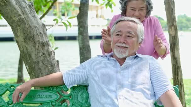 Édes Senior pár pihentető parkban. Régi ázsiai ember ül a padon, és öregasszony jön, és meglepni őt. Senior életmód koncepció.