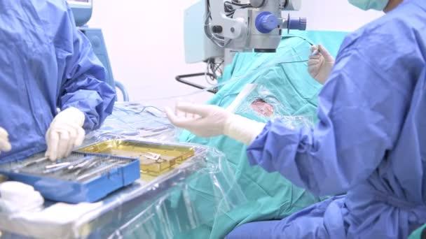 Augenarzt bei der Arbeit. junger kaukasischer Chirurg mit seiner schönen chinesischen Assistentin, die eine ältere Patientin operiert. echter Operationssaal. medizinisches Konzept.