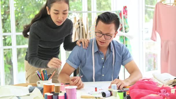 Fashion designer at work. Young chinese man and woman fashion designer and tailor drawing design concept in note book at their home office. Small business start up concept.