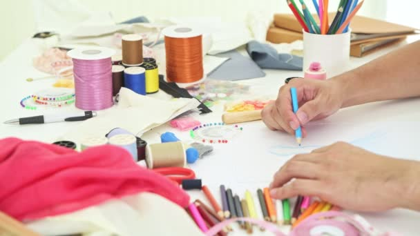 Young fashion designer drawing his concept. Young chinese gay man start his small fashion design house, drawing fashion design on paper. Small business, sme, start up concepts.