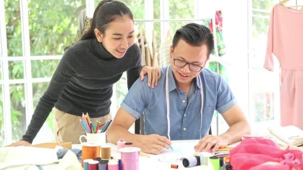 Modedesignerin bei der Arbeit. junge chinesische Mann und Frau Modedesignerin und Schneiderin zeichnen Designkonzept in Notizbuch in ihrem Homeoffice. Konzept zur Gründung kleiner Unternehmen.