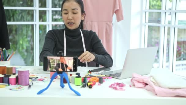 Fashion designer at work. Young chinese fashion designer and tailor doing a video blog and video review at her home office. Small business start up concept.