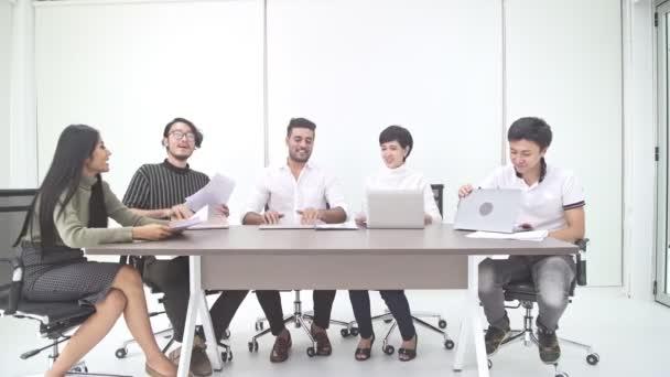 Obchodní jednání. Malý, nastartujte na obchodní jednání v pokoji. Asijský tým s kostým Indián dokončí jejich setkání, zavřít laptop a vyvolané papíru. Nový obchodní model nastartovat pojmy
