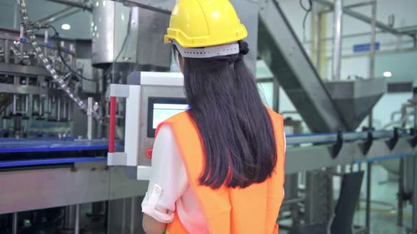 Woman industrial engineer at work in factory. Beautiful young chinese engineer working in large factory. With safety helmet and jacket. High tech automatic machine in background.