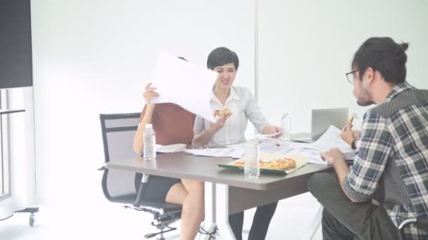 Business meeting. Small start up business lunch meeting in room. Asian team with men and women brainstorming, sitting down eating pizza for lunch. New business model start up concepts.