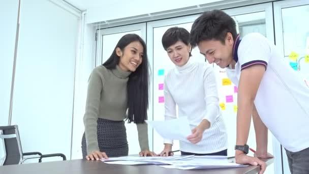 kleine Teambesprechung. Gruppe asiatischer Geschäftsleute beim Brainstorming mit Dokumenten auf dem Tisch. Multi Ethic Business Team Gründerkonzept.