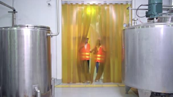 Ženy průmyslové inženýry při práci v továrně. Krásná mladá čínští inženýři pracují ve velké továrně. S ochrannou přilbu a sako. High-tech automat v pozadí