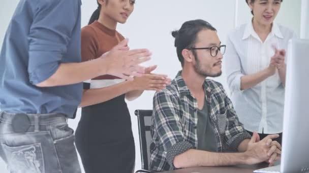 Obchodní jednání. Malá začínající skupinové diskuse v pokoji. Asijský mladík předložit jeho tým na jeho myšlenku v počítači. Nový obchodní model nastartovat pojmy.