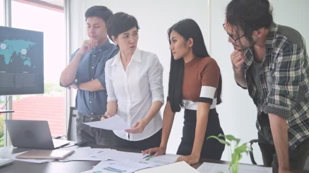 Business meeting. Small start up business meeting in room. Asian team with men and women brainstorming the next big idea, standing up. New business model start up concepts.