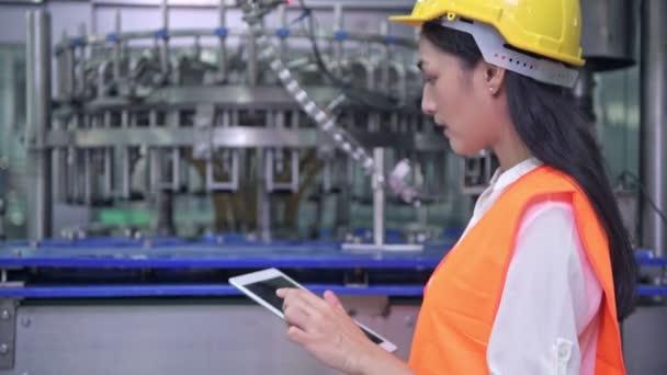 Žena inženýr v práci v továrně. Krásné mladé čínské inženýr pracující ve velké továrně. S ochrannou přilbu a sako. High-tech automat v pozadí