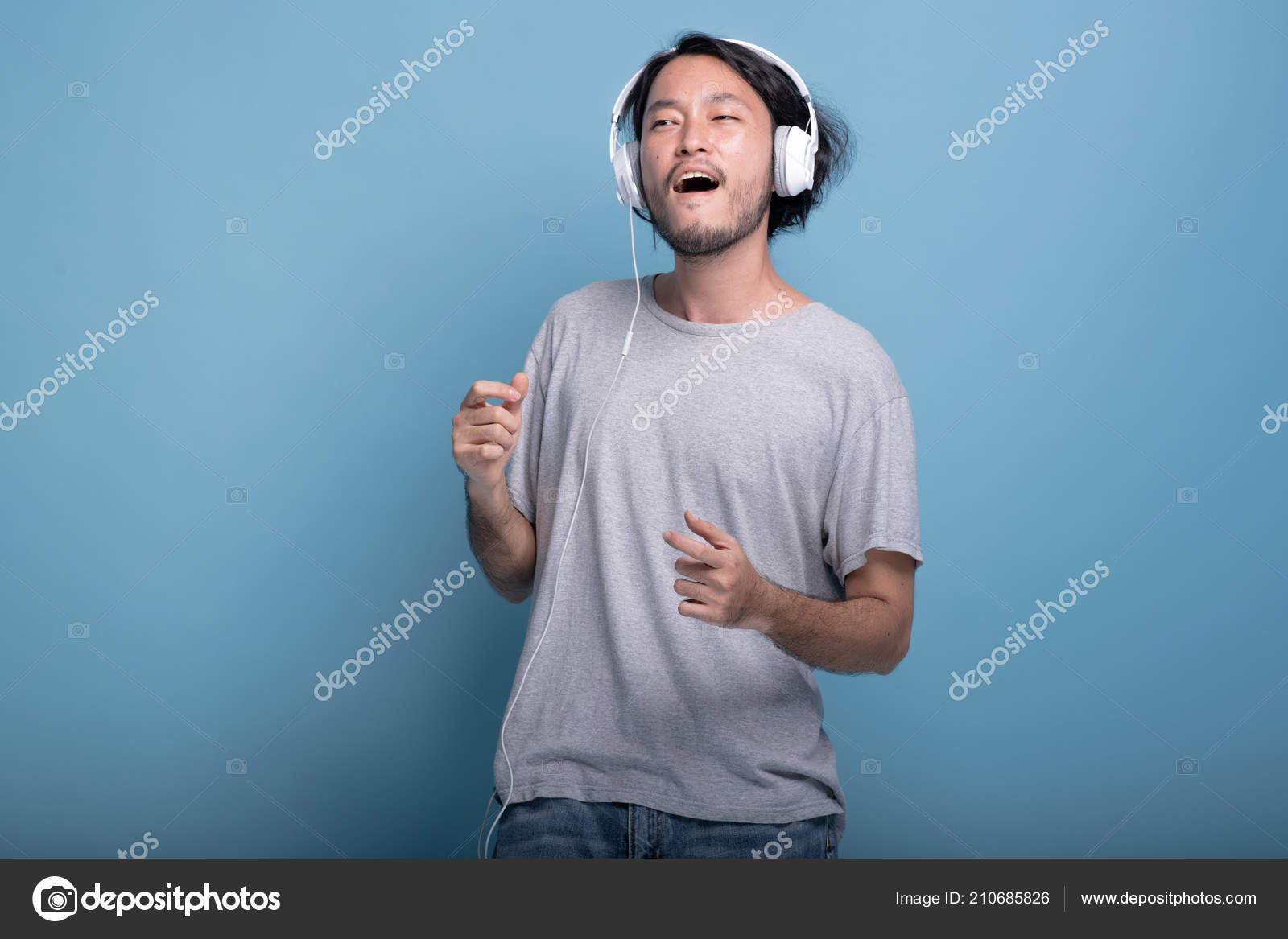 Young Bearded Man Listening Music Blue Background Very Happy