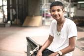 Gördeszkás portré. Mosolyogva ázsiai fiú városi gördeszka Park ül a koszos beton híd alatt. Természetes fény beállítás.