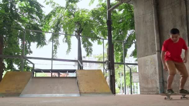 Slow-Motion der asiatische Teenager tun Trick auf Skateboard Skatepark