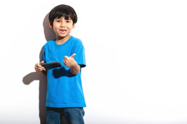 Young boy playing mobile game portrait in white background with hard light. Mixed race boy in blue shirt and jean. Thumb up.