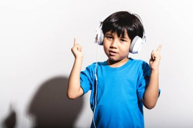 Young boy listening to music portrait in white background with hard light. Mixed race boy in blue shirt and jean. Finger up dancing.