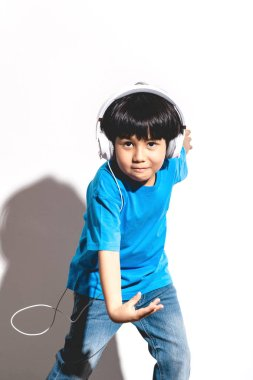 Young boy listening to music portrait in white background with hard light. Mixed race boy in blue shirt and jean. Dancing.