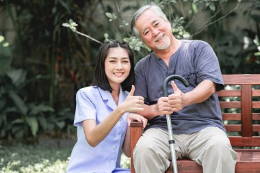 Nurse with patient sitting on bench together with thumbs up. Asian old man and young woman sitting together talking. Very happy mood.
