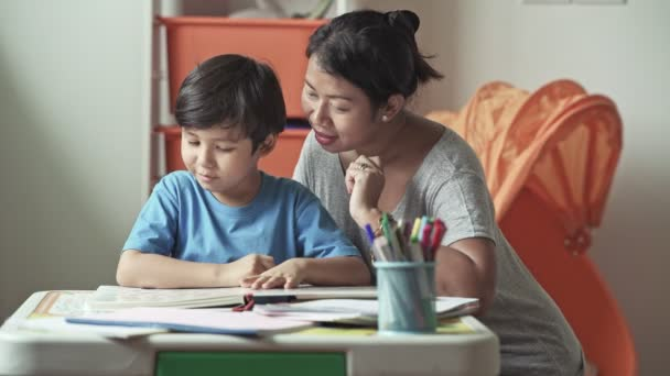 mother showing son pictures in book and teaching to read at home