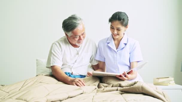 mladá Asijská Sestra čtení knihy s zralé asijské muže s šedými vlasy v nemocnici a pak při pohledu do kamery a usmívá se