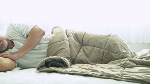 asijské muži s šedými vlasy, spí v posteli pod dekou