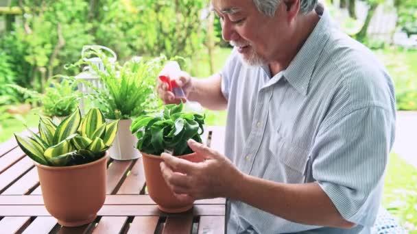 Senior asiatischen Mann Blumen in Töpfen an Holztisch im Garten Gießen