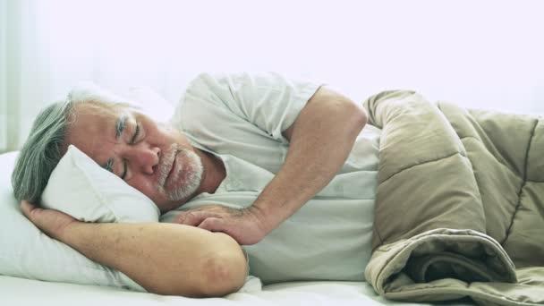 asijské muži s šedými vlasy, spí v posteli pod dekou na bílém pozadí