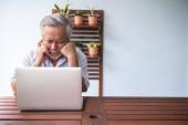 alter Mann versucht, Computer auf dem Balkon im Freien zu benutzen. asiatischer Mann mit weißem Bart mit Laptop, aufgewühlte Stimmung. Senioren-Lebensstil-Konzept.
