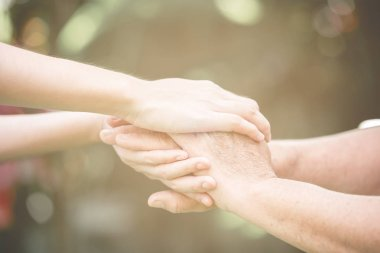 Comforting hand. Young nurse holding old man's hand in outdoor garden standing up. Senior care, care taker and senior retirement home service concept.